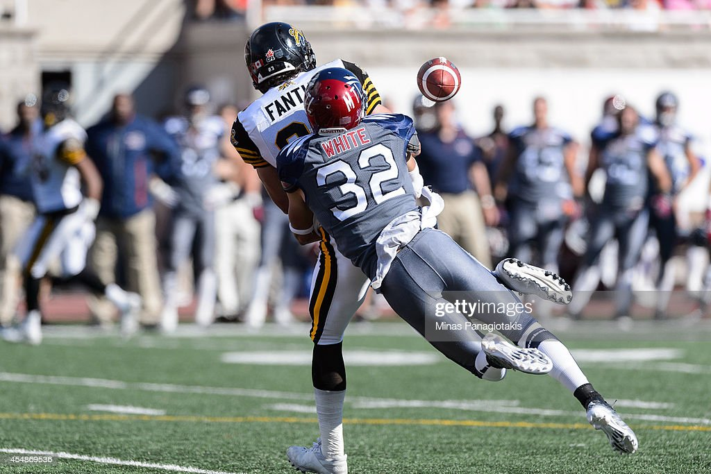 Mitchell White #32 of the Montreal Alouettes tackles Andy Fantuz #83 of the Hamilton Tiger-Cats during the CFL game at Percival Molson Stadium on September 7, 2014 in Montreal, Quebec, Canada. The Alouettes defeat the Tiger-Cats 38-31.
