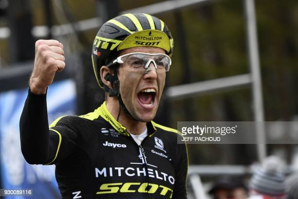Mitchelton-Scott cycling team's Simon Yates from Great Britain celebrates as he crosses the finish line at the end of the seventh stage of the Paris...