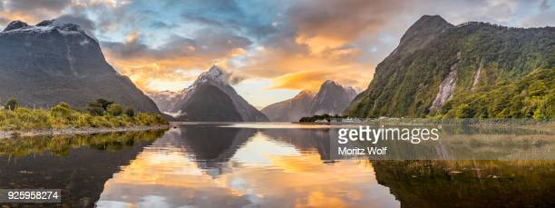 mitre peak reflecting in the water, sunset, milford sound, fiordland national park, te anau, southland region, southland, new zealand - international landmark stock pictures, royalty-free photos & images