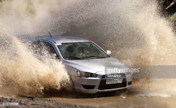 mitsubishi car rides through puddle - goop brand name stock pictures, royalty-free photos & images