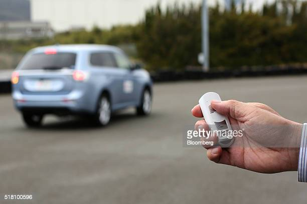 Mitsubishi Electric Corp employee uses a remote control during a demonstration of the company's selfdriving vehicle in Ako Hyogo Prefecture Japan on...