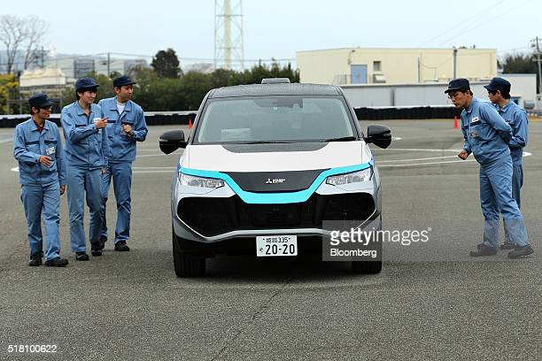 Mitsubishi Electric Corp employees check the company's selfdriving vehicle during a demonstration in Ako Hyogo Prefecture Japan on Friday March 18...