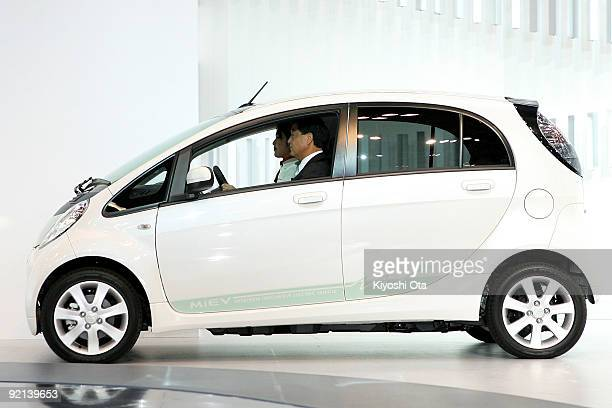 Mitsubishi Motors Corp President Osamu Masuko rides the company's electric vehicle 'iMiEV' during the 41st Tokyo Motor Show at Makuhari Messe on...