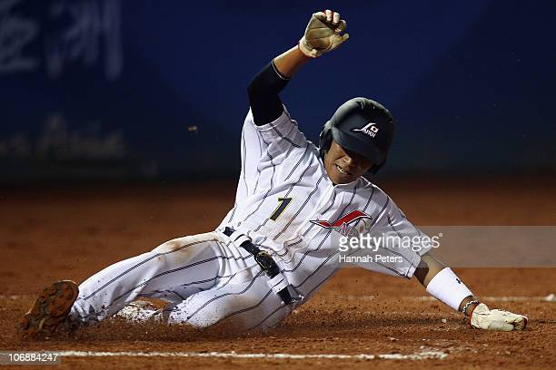 Mitsugu Kitamichi of Japan dives into socre a home run during the Men's Preliminary match between Japan and China at Aoti Baseball Field 1 during day...