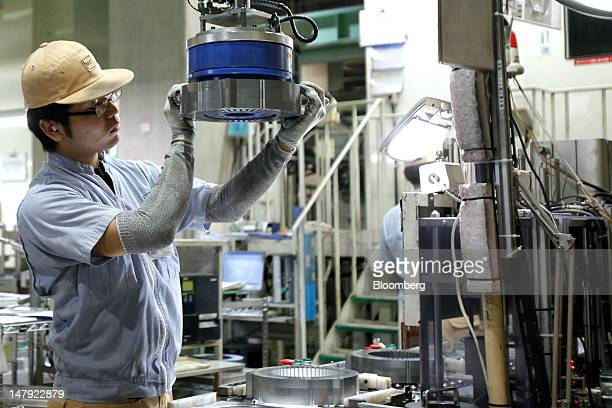 A Mitsui Hightec Inc employee packs a motor core used for Toyota Motor Corp's hybrid vehicles after its final inspection on the production line at...
