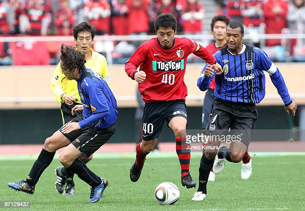 Mitsuo Ogasawara of Kashima Antlers and Lucas of Gamba Osaka compete for the ball during the Xerox Super Soccer match between Kashima Antlers and...