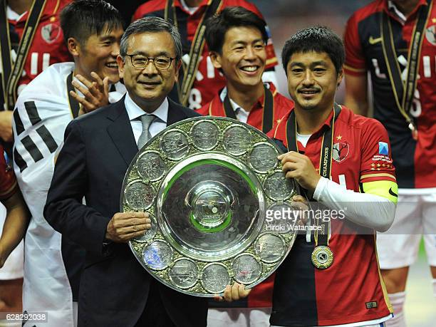 Mitsuo Ogasawara of Kashima Antlers and Mitsuru Murai hold up the trophy after the J.League Championship Final second leg match between Urawa Red...