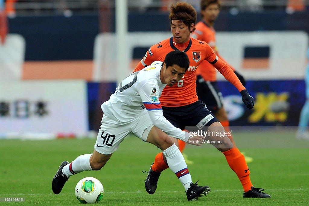 Mitsuo Ogasawara of Kashima Antlers and Takuya Aoki of Omiya Ardija compete for the ball during the J.League match between Omiya Ardija and Kashiwa Reysol at Nack 5 Stadium Omiya on March 30, 2013 in Saitama, Japan.