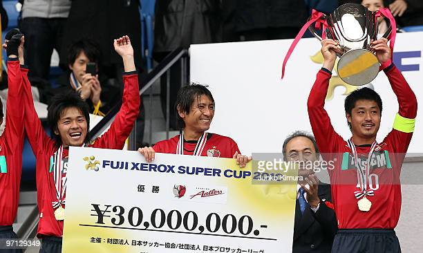 Mitsuo Ogasawara of Kashima Antlers celebrates with his team-mates and the trophy after the Xerox Super Soccer match between Kashima Antlers and...