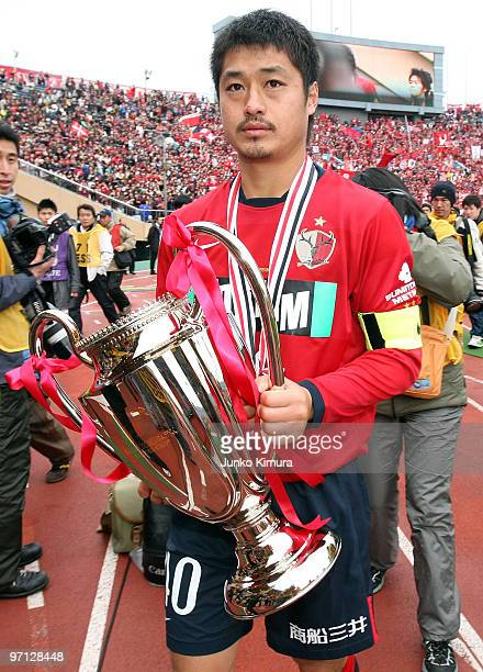 Mitsuo Ogasawara of Kashima Antlers holds the trophy after the Xerox Super Soccer match between Kashima Antlers and Gamba Osaka at the National...