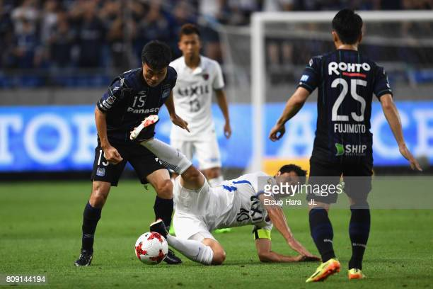 Mitsuo Ogasawara of Kashima Antlers is challenged by Yasuyuki Konno of Gamba Osaka during the JLeague J1 match between Gamba Osaka and Kashima...