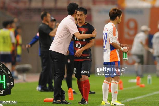 Mitsuo Ogasawara of Kashima Antlers is embraced by head coach Go Oiwa after substituted during the JLeague J1 match between Kashima Antlers and...