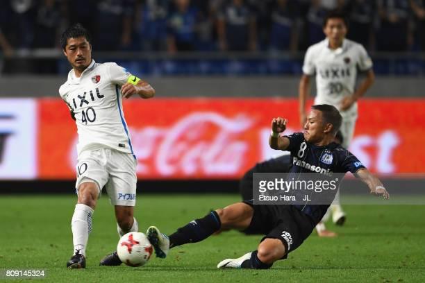Mitsuo Ogasawara of Kashima Antlers is tackled by Yosuke Ideguchi of Gamba Osaka during the JLeague J1 match between Gamba Osaka and Kashima Antlers...