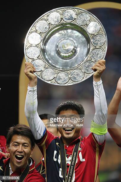 Mitsuo Ogasawara of Kashima Antlers lifts the JLeague shield trophy after victory in the JLeague Championship Final second leg match between Urawa...