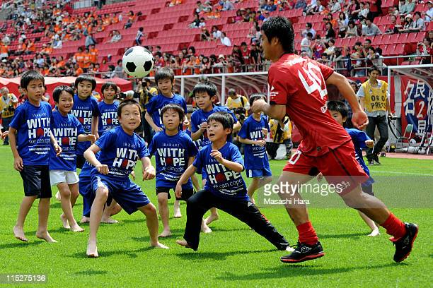 "Mitsuo Ogasawara of Kashima Antlers plays with children during the ""Smile Again Yell From Kashima"" charity match at Kashima Stadium on June 4, 2011..."