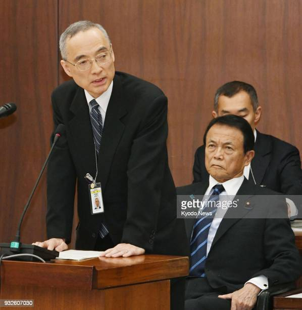 Mitsuru Ota financial bureau chief of Japan's Finance Ministry speaks as Finance Minister Taro Aso watches during a House of Representatives...