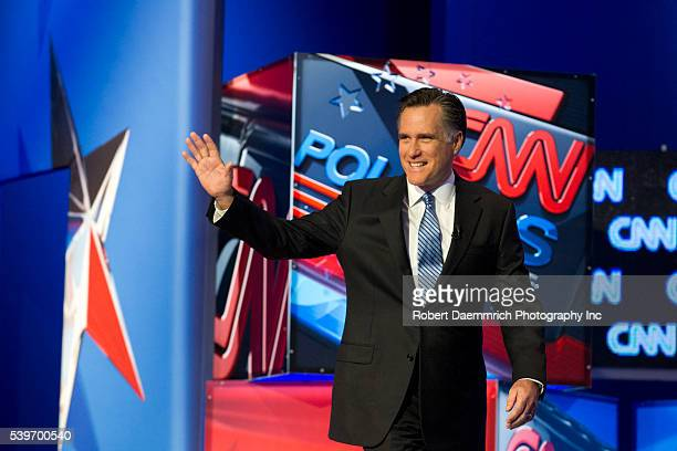 Mitt Romney arrives onstage as the four remaining Republican presidential candidates appear January 19, 2012 at the CNN Debate in North Charleston,...