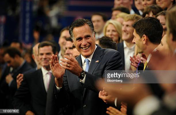 Mitt Romney Republican presidential candidate center and Representative Paul Ryan vice presidential candidate center right applaud during a group...