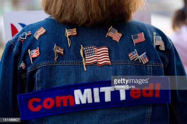 Mitt Romney supporter stands outside a caucus location before Republican presidential candidate former US Sen Rick Santorum was to speak during a...