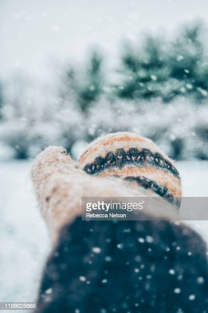 mittened hand reaching out to catch snowflakes - mitten stock pictures, royalty-free photos & images