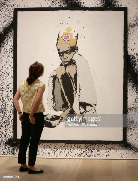Mitzi Mina from Sotheby's looking at Banksy's work 'Burger King' , at a press preview for the exhibition Banksy: The Unauthorised Retrospective,...