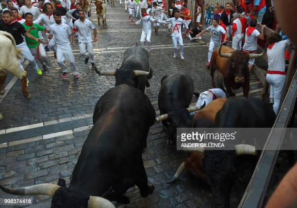 Miura fighting bulls fall during the last bullrun of the San Fermin festival in Pamplona northern Spain on July 14 2018 Each day at 8am hundreds of...