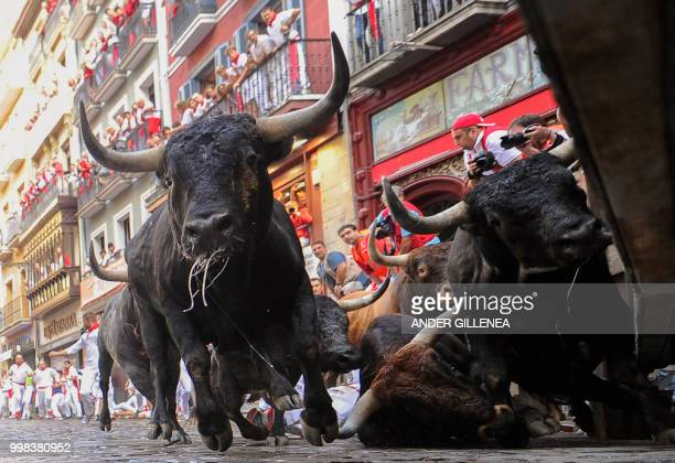 TOPSHOT Miura fighting bulls fall on the last bullrun of the San Fermin festival in Pamplona northern Spain on July 14 2018 Each day at 8am hundreds...