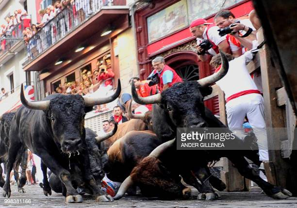 Miura fighting bulls fall on the last bullrun of the San Fermin festival in Pamplona northern Spain on July 14 2018 Each day at 8am hundreds of...