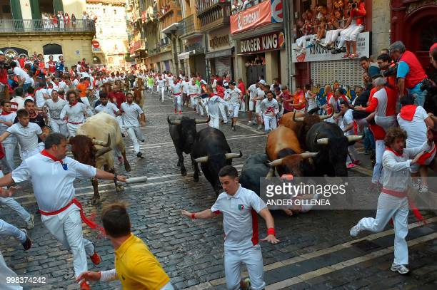 Miura fighting bulls fall over a runner on the last bullrun of the San Fermin festival in Pamplona northern Spain on July 14 2018 Each day at 8am...