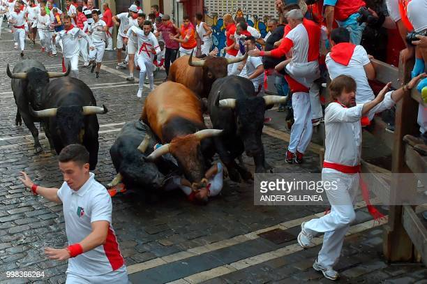 Miura fighting bulls run over a reveller on the last bullrun of the San Fermin festival in Pamplona northern Spain on July 14 2018 Each day at 8am...