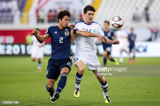 Miura Genta of Japan competes for the ball with Eldor Shomurodov of Uzbekistan during the AFC Asian Cup Group F match between Japan and Uzbekistsn at...
