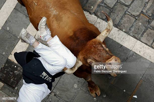 Miura's fighting bull horns a runner at Calle Estafeta during the ninth day of the San Fermin Running Of The Bulls festival on July 14 2014 in...