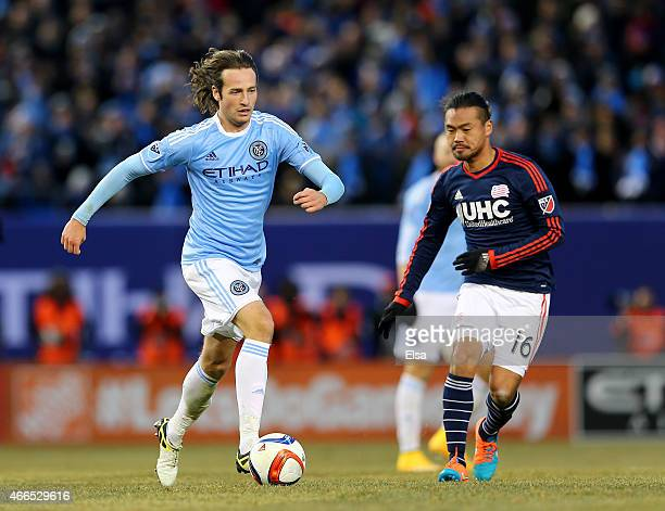 Mix Diskerud of New York City FC takes the ball as Daigo Kobayashi of New England Revolution defends during the inaugural game of the New York City...