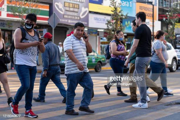 A mix of mask and unmasked people cross the street in main downtown commercial area on March 26 2020 in Monterrey Mexico While most countries and...
