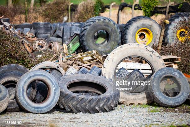 a mix of old car, lorry and tractor tyres stacked up in a farmyard - obsolete stock pictures, royalty-free photos & images
