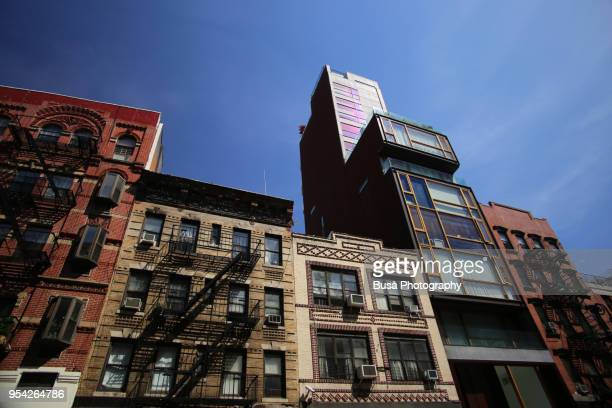 mix of old walkups and new luxury condominium building in orchard street in the lower east side, manhattan, new york city, usa - manhattan new york city stock pictures, royalty-free photos & images