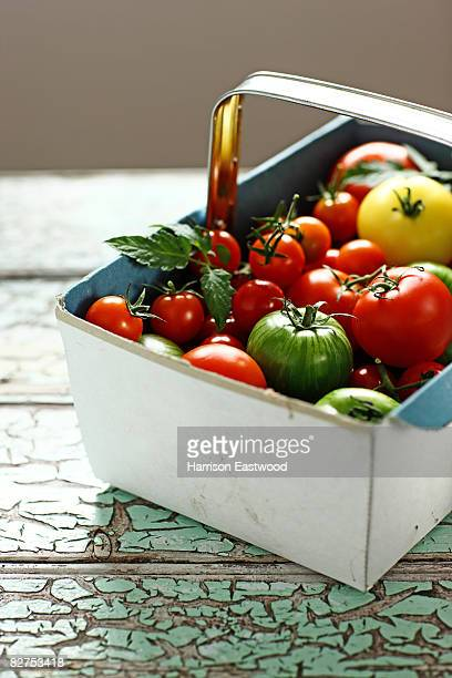 mix of tomatoes in punnet on wooden table