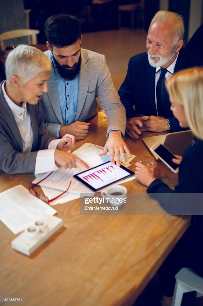 Mixed age business team having a meeting in cafe. : Stock Photo