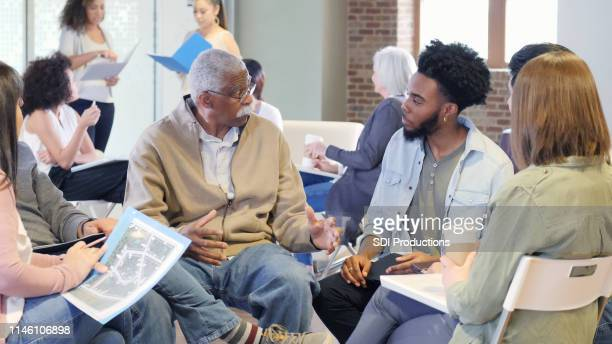 mixed age group discusses racial issues - community centre stock pictures, royalty-free photos & images