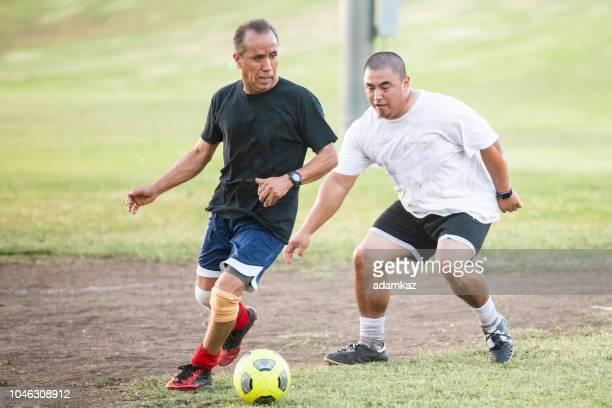 gemengde leeftijd groep latino mannen te voetballen - verdediger voetballer stockfoto's en -beelden