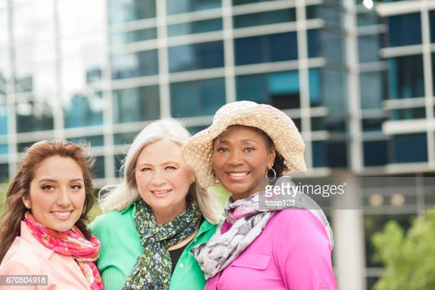Mixed age, multi-ethinc group of women friends in downtown city area.