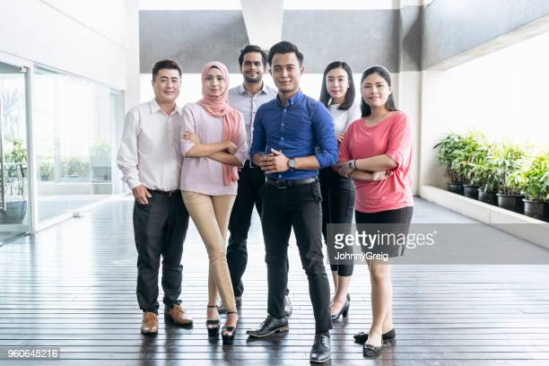 mixed age range business colleagues in modern office - malaysia stock pictures, royalty-free photos & images