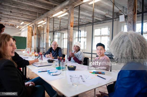 mixed business team discussing during a creative workshop - lucy lambriex stockfoto's en -beelden