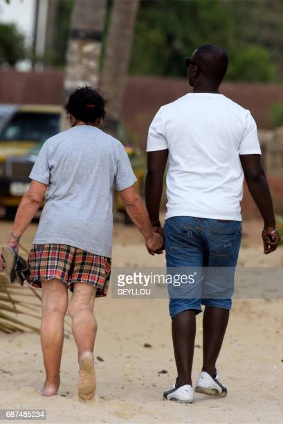 MAHONY A mixed couple walks on the beach of Kololi on April 9 2017 For decades The Gambia has built a reputation as a haven for tourists willing to...