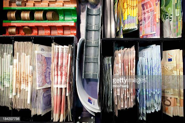 Mixed denomination currency banknotes including euros bottom right and sterling left are seen in a cash register at a Travelex store operated by Apax...
