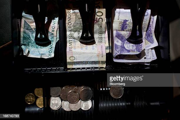 Mixed denomination Swedish kronor notes and coins sit in a cashier's till inside a currency exchange in Malmo, Sweden, on Tuesday, May 14, 2013....