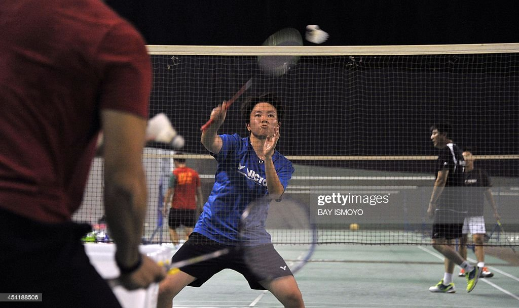 Mixed doubles badminton player Liliyana Natsir (C) of Indonesia practices with his coach Richard Mainaky (L) in Jakarta on August 26, 2014 in preparation for the 17th Asian Games in Incheon from September 19 to October 4. Indonesia is targeting their medal hopes in badminton in the top Asian sporting event. AFP PHOTO / Bay ISMOYO