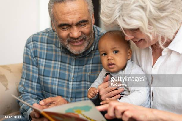 mixed ethnic grandparents spending time with their granddaughter - fat granny stock pictures, royalty-free photos & images