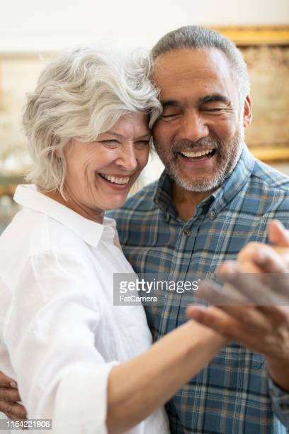 mixed ethnic senior couple dancing together - mixed race person stock pictures, royalty-free photos & images