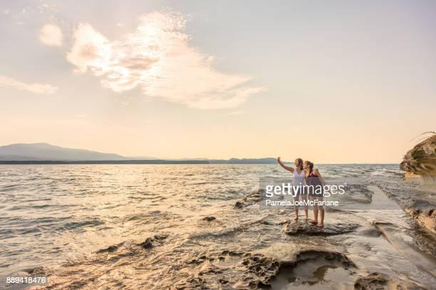 Mezcla a étnicas hermanas posando para Selfie en desierto océano playa